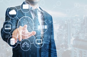 Double exposure of professional businessman connected devices with world digital technology internet and wireless network on touch screen and city of business background in business and technology concept