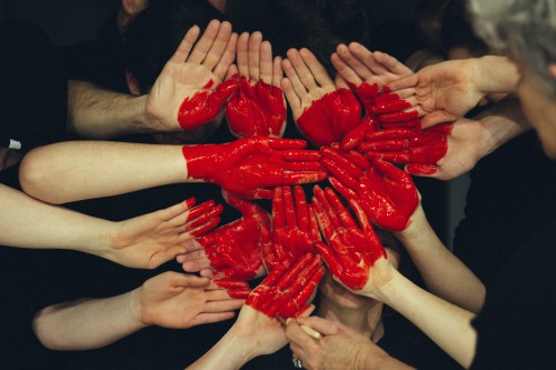 Hands of people shaping a red heart